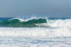La persona que practica surf que practica surf limpia hacia fuera la onda Fotos de archivo libres de regalías