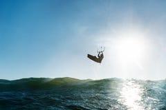 La persona que practica surf que salta delante del sol Fotos de archivo libres de regalías