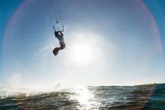 La persona que practica surf que salta delante del sol Imagenes de archivo
