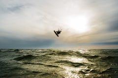 La persona que practica surf que salta en la puesta del sol Imágenes de archivo libres de regalías