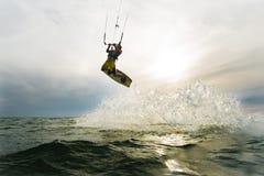 La persona que practica surf que salta en la puesta del sol Fotografía de archivo libre de regalías