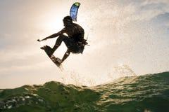 La persona que practica surf que salta delante de la puesta del sol Imagen de archivo