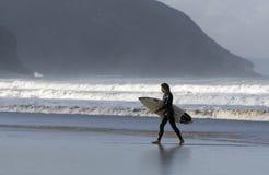 La persona que practica surf se niega a afrontar ondas con la tabla hawaiana Foto de archivo