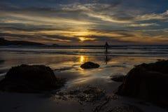 La persona que practica surf solitaria camina en el mar debajo de un cielo dramático de la puesta del sol imagenes de archivo