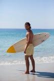 La persona que practica surf sonriente con la tabla hawaiana que se coloca en la playa costea Fotos de archivo libres de regalías