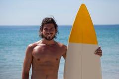La persona que practica surf sonriente con la tabla hawaiana que se coloca en la playa costea Foto de archivo libre de regalías