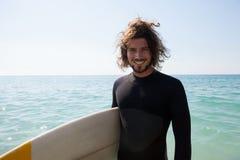 La persona que practica surf sonriente con la tabla hawaiana que se coloca en la playa costea Fotografía de archivo libre de regalías