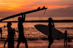La persona que practica surf y la puesta del sol Foto de archivo