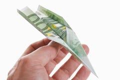 La persona que sostenía el aeroplano de papel dobló a partir de billete de banco del euro el 100 Imagen de archivo libre de regalías