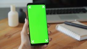 La persona que usa el teléfono móvil con greenscreen la exhibición a disposición almacen de metraje de vídeo