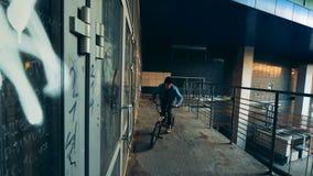 La persona salta en una bici en el edificio, cierre para arriba metrajes