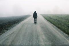 La persona se coloca en la carretera de asfalto de niebla fotografía de archivo libre de regalías