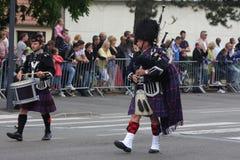 La persona se vistió en vestido tradicional del escocés que marchaba para el día nacional del 14 de julio, Francia Imagenes de archivo