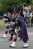 La persona se vistió en vestido tradicional del escocés que marchaba para el día nacional del 14 de julio, Francia Foto de archivo libre de regalías