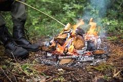 La persona si riscalda dal fuoco nella foresta Immagini Stock Libere da Diritti
