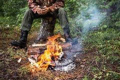 La persona si riscalda dal fuoco nella foresta Immagini Stock