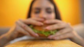 La persona sirve la hamburguesa a la muchacha hambrienta, la consumición femenina con avaricia y el apetito metrajes
