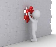 La persona sta completando il puzzle della parete Immagine Stock