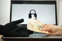 La persona sta dando i soldi al pirata informatico di computer agli archivi di decrypt, comp. Fotografia Stock