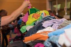 La persona sta esaminando il mercato delle pulci dei vestiti fotografia stock