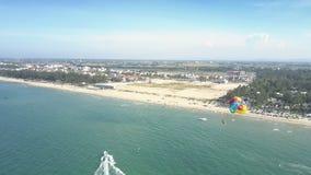 La persona superiore con il paracadute sorvola l'oceano contro la città archivi video
