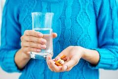 La persona tiene la medicina e un bicchiere d'acqua in sue mani Fotografie Stock