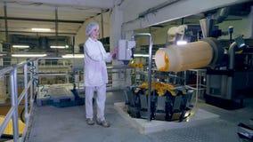 La persona trabaja con una máquina de la fábrica, controlando un transportador con los microprocesadores almacen de video