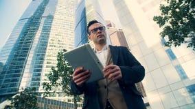 La persona trabaja con una tableta en un fondo de los rascacielos, visión inferior metrajes