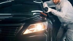 La persona utiliza el equipo de pulido mientras que trabaja en un servicio del coche 4K metrajes