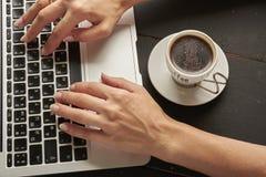 la persona utiliza un ordenador portátil con una taza de café Fotos de archivo