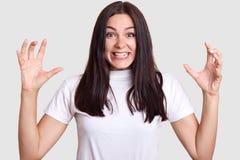 La personne émotive sur le fond gris, femelle mêmes avec les cheveux foncés et de grands yeux bruns sans rien composent l'essai p image stock