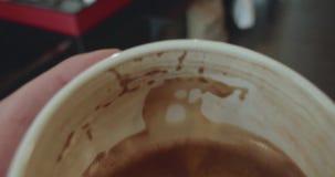 La personne abaisse la tasse de café à moitié pleine après le boire banque de vidéos