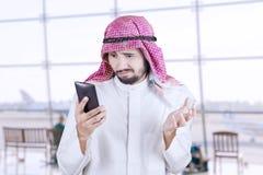 La personne Arabe lit le message dans l'aéroport Photographie stock libre de droits