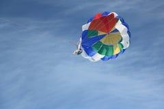 La personne avec un parachute sur un vol de câble dans le ciel Photos stock