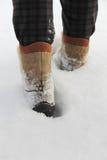 La personne dans les bottes va sur une neige profonde Photo libre de droits
