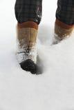 La personne dans les bottes va sur une neige profonde Image libre de droits
