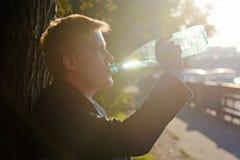 La personne dans un costume boit dans l'eau d'été d'une bouteille Photos stock