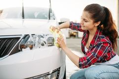 La personne féminine avec l'éponge nettoie le phare de véhicule image stock