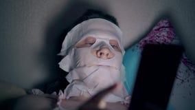La personne fixe le masque blanc de feuille sur des yeux de joue et de petits pains banque de vidéos