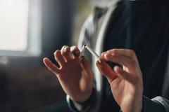 La personne masculine dépendante casse une cigarette image stock