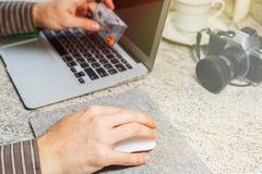La personne masculine fait l'achat en ligne avec la carte de crédit photos libres de droits