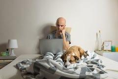 La personne masculine s'assied avec l'ordinateur portable dans le lit avec le chien de sommeil Photographie stock libre de droits