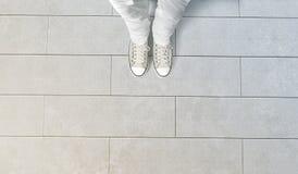La personne prenant la photo de ses pieds se tiennent sur le plancher en béton Photographie stock libre de droits