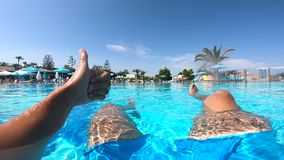 La personne renonce à des pouces tout en se reposant dans une piscine près de l'hôtel Concept de vacances d'?t? clips vidéos