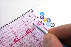 La personne tient un stylo complétant les nombres sur un billet de loterie Images libres de droits