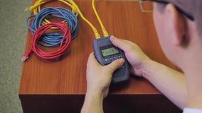 La personne travaille avec l'appareil de contrôle de LAN de câble de réseau banque de vidéos