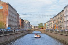 La perspectiva de un canal y de un barco de placer flota bajo bridg Foto de archivo