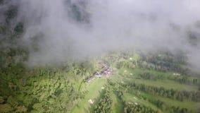 la perspectiva del Pájaro-ojo del campo de golf en medio del bosque, la opinión de los golf-vínculos abre a través de las nubes almacen de video