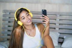 La pertenencia étnica latina asiática joven de la mujer hermosa y feliz del estudiante mezcló escuchar la música con los auricula Imágenes de archivo libres de regalías
