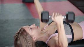 La pesa de gimnasia atlética hermosa de la chica joven ejercita los músculos pectorales en el gimnasio almacen de video